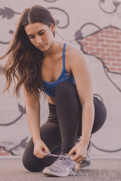 athletic model tying her shoes