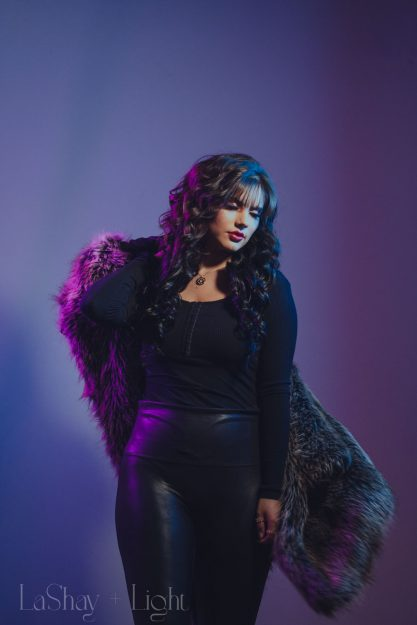 High fashion model with purple and blue lights swinging fur coat